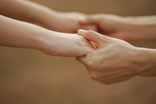 Picture of couple holding hands and of just hands for healing with topicals and salves for Cortesia Herbal Products