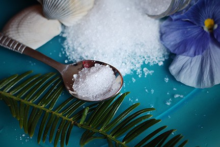 Coarse salt and magnesium source on surface in spoon and spilled with tropical elements for tips for wellness